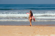 surfer girl in bikini with white surfboard on a beach go to the