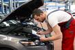 Automechaniker kontrolliert Fahrzeug in einer Werkstatt // car mechanic controlled vehicle in garage