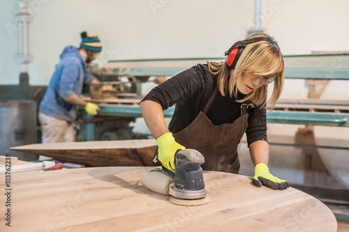 Fotografering Female carpenter Using Electric Sander / Female carpenter Using Electric Sander