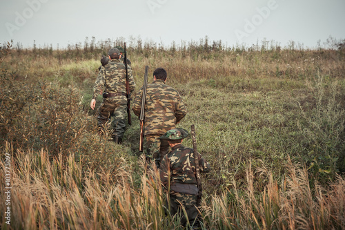 Foto op Canvas Jacht group of hunters going up in the early morning in a rural field through the tall grass during hunting