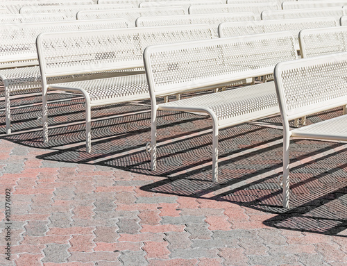 Groovy Neat Rows Of White Metal Benches On Brick Pavement For Alphanode Cool Chair Designs And Ideas Alphanodeonline