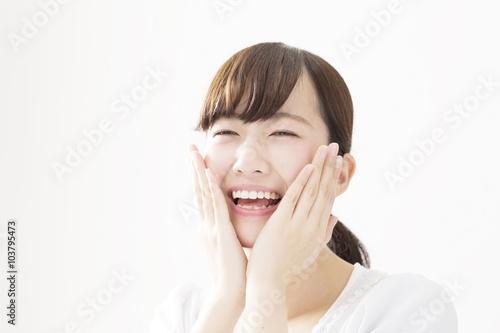 Fotografering  若い女性 感情 笑顔 笑う 嬉しい ほほに両手をあてる 白バック コピースペース
