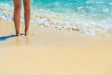 Closeup Of Female Legs On Tropical Beach. Women's Legs On The Sa