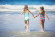 Cute little girls playing at the beach together during summer vacation