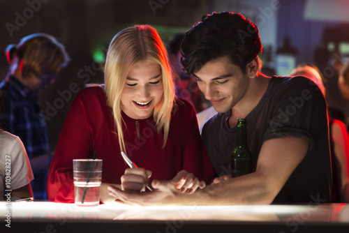 Photo Young man is flirting with attractive woman at bar writing number on his hand