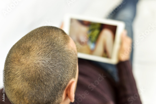 Fotografia  young man watching porn in his tablet