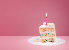 Slice Of Birthday Cake With Candle On Pink