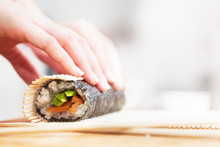 Preparing, Rolling Sushi. Salmon, Avocado, Rice And Chopsticks On Wooden Table.