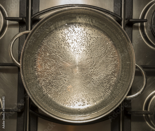 Fotografering  Boiling water for cooking in a metal pan on a stove , cooker
