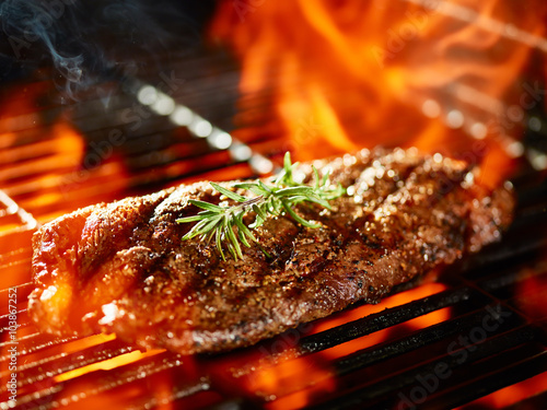 flat iron steak cooking on flaming grill with rosemary garnish - 103867252