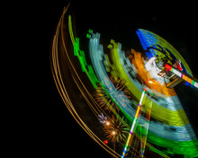 Night Shot Of A Carnival Ride In Motion With Colorful Lights Sweeping Through The Sky With Fireworks Behind It In The Distance. Slow Shutter Speed Blurs Colors From The Ride's Movement.