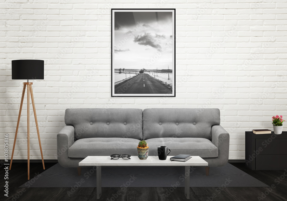 Road picture in vertical art frame on wall. Sofa, lamp, plant, glasses, book, coffee on table in living room interior.