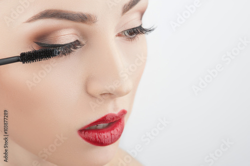 Valokuva  Attractive girl is putting on make-up