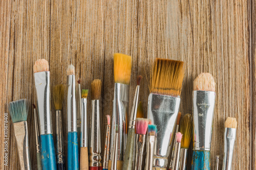 Artist paint brushes over rustic wooden texture