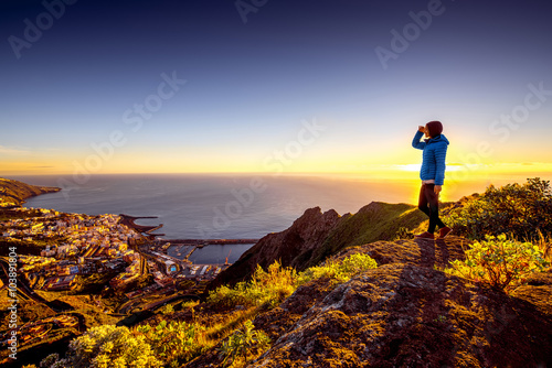 Poster Canary Islands Young female traveler in blue jacket enjoying landscape view on Santa Cruz city on La Palma island in the morning