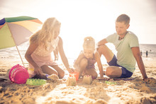 Happy Family Playing On The Beach And Build Some Sand Castle