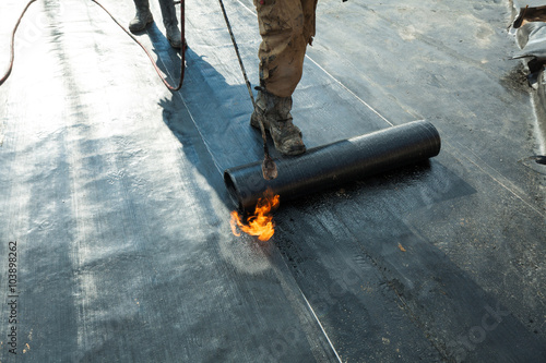 Installation of roll roofing waterproofing propane blowtorch during construction Canvas Print