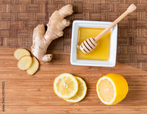 Photo  Fresh ginger root,  lemon and honey on wooden cutting board