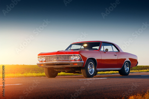 Retro red car stay on asphalt road at sunset