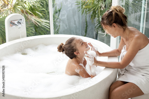Photo Mother with a child washing in bath