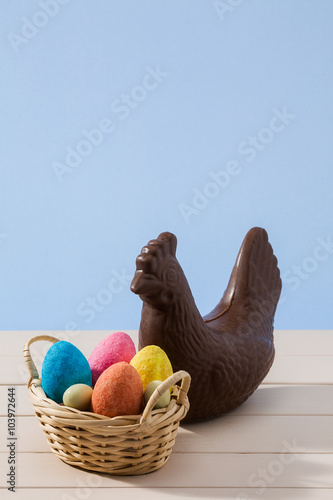 Aluminium Prints Grocery Easter chocolate chicken and colored eggs over a white table