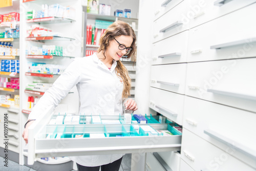 Spoed Foto op Canvas Apotheek Female pharmacist taking a medicine from a shelf - Doctor opening a drawer in her pharmacy