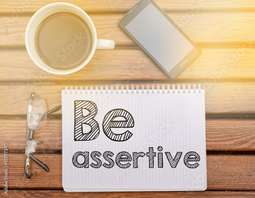 Photo Notebook on table with text about soft competence: Be assertive