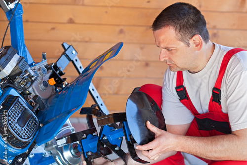 Foto  Man installing tilling accessory on agricultural machine