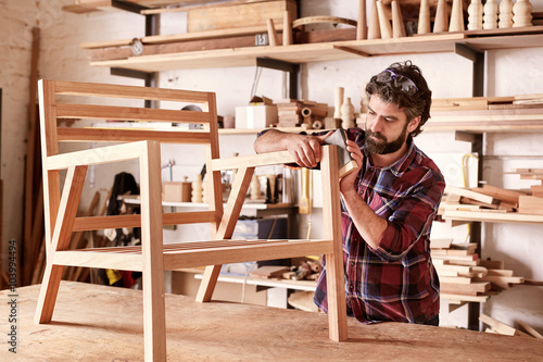 Furniture designer sanding a wooden chair frame