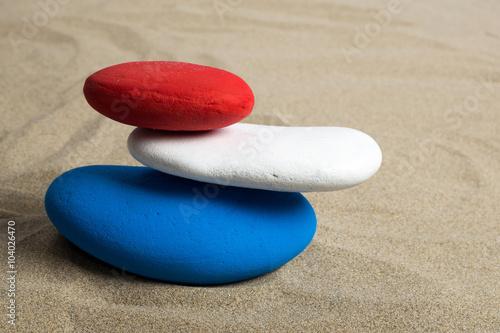 Photo sur Plexiglas Zen pierres a sable Pile de galets colorés, bleu, blanc, rouge aux couleurs de plusieurs drapeaux nationaux,