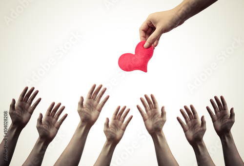 Vászonkép Many hands chasing, fighting to get a red heart - fighting for love concept