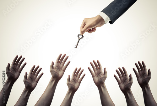 Fényképezés hand of a businessman giving a key to many hopeless hands - giving help, opportu