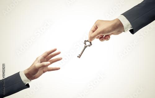 hand of a businessman giving a key to many hopeless hands - giving help, opportu Tapéta, Fotótapéta