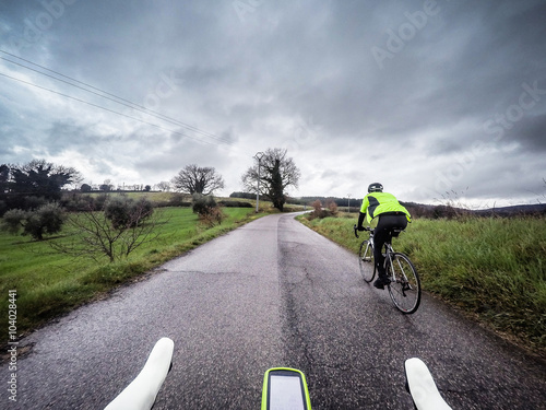 Foto op Plexiglas Fietsen couple of cyclists in an uphill road during a storm. POV Original point of view