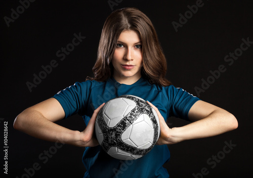 young female soccer player standing and holding the ball