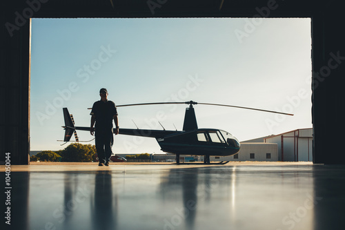 Fotografia Pilot walking away from helicopter