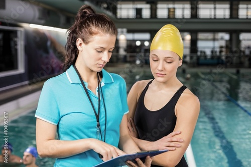 Photo  Trainer woman showing clipboard at a swimmer