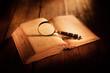 Leinwandbild Motiv libro antico con lente d'ingrandimento