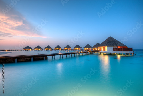Water villas on Maldives resort island in sunset Wallpaper Mural