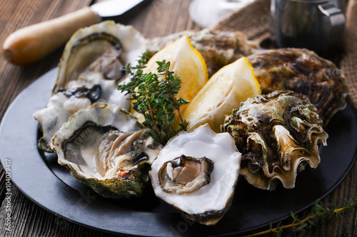 Fotografija  Fresh Oysters in shell with lemon