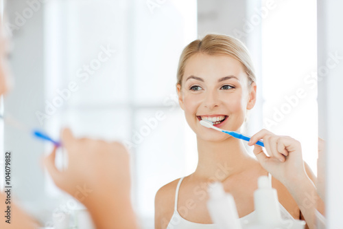 Cuadros en Lienzo woman with toothbrush cleaning teeth at bathroom