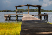 Wooden Pier Above Grass Leading To Empty Boathouse Shelter Structure With Bench On Water River Lake Intracoastal Waterway Looking Peaceful Serene Tranquil