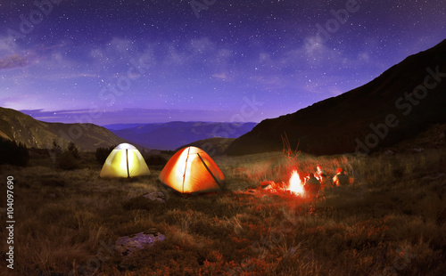 Photo Stands Camping Illuminated yellow camping tent under stars at night