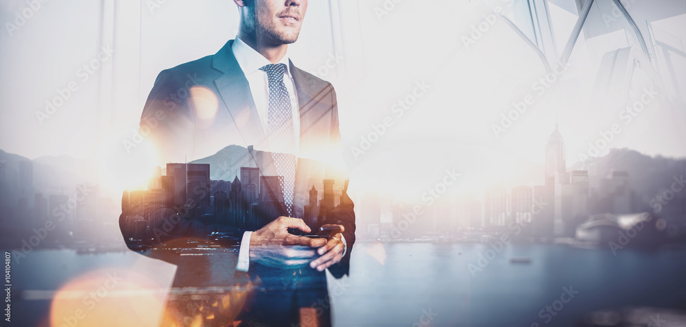 Fototapeta Photo of  businessman holding smartphone. Double exposure, city on the background. Wide