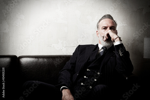 Fotografía Portrait of adult gentleman wearing trendy suit and sitting modern studio on leather sofa against the empty concrete wall