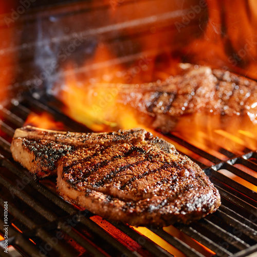 Fotografiet ribeye steaks on the grill over the open flame