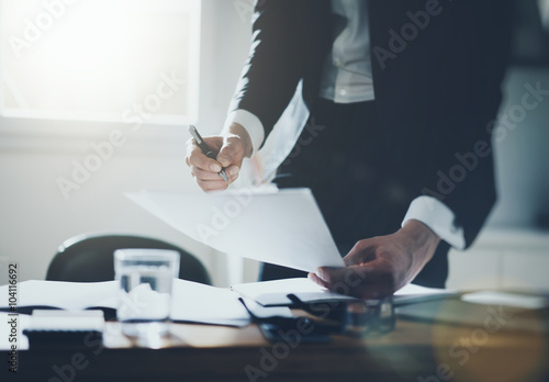 Fotografía  Businessman signing documents in office wearing black suite and white shirt