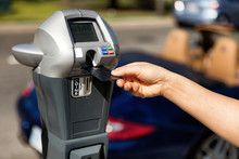 Hand Putting Credit Card Into Parking Meter For Time