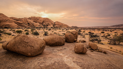 Typical round stones in the Namibian savanna at sunset