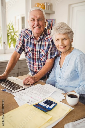 Portrait of senior couple checking their bills - 104148200